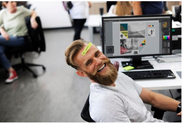 man laughing at desk